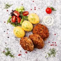 verse, zelfgemaakte gehaktballen, geserveerd met tomatensalade en nieuwe pota