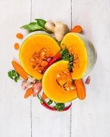 ingrediënt voor pompoensoep, kruiden met groenten op witte houten foto