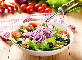 olie gieten in kom salade foto