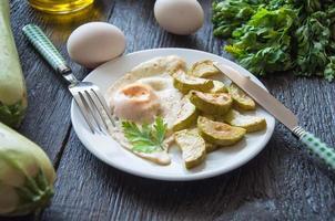 gebakken eieren en gehakte courgette met peterselie op het bord foto