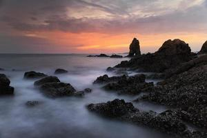 golven spatten op de rotsen foto