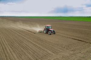 boer zaaien gewassen op veld met trekker foto