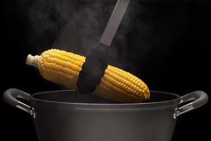 hete maïs uit pot met stoom op zwarte achtergrond foto