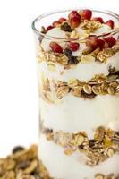 glas muesli met fruit en yoghurt op wit wordt geïsoleerd foto