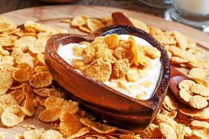 cornflakes met melk in een houten kom foto
