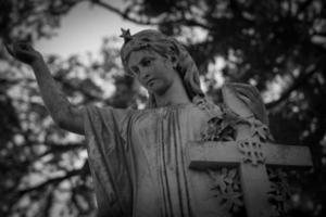 standbeeld van vrouw met kruis foto