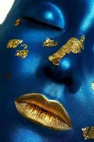 vrouwelijk model met blauwe huid en gouden lippen. halloween make-up