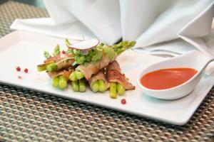 asperges gewikkeld in spek met Italiaanse saus foto