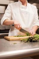 vrouwelijke chef-kok hakken asperges in commerciële keuken foto