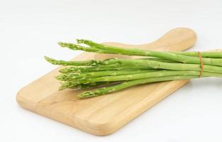 asperges en snijplank geïsoleerd op een witte achtergrond foto