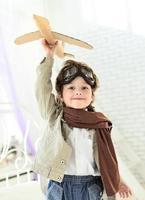 gelukkige jongen met jet vliegtuig in de hand foto