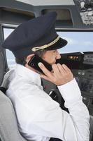 piloot in de cockpit met behulp van mobiele telefoon tegelijkertijd foto