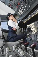 vrouwelijke piloot denken welke knop te drukken in de cockpit van het vliegtuig