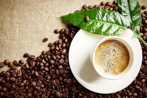 koffiekopje schuim op vlas met groene bladeren, bonen foto