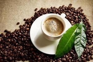koffiekopje schuim, bonen in de hoek, groen blad op linnen foto