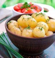 jonge gekookte aardappelen met dille in olie op de kom foto