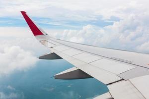 vleugel van een vliegtuig dat boven de wolken vliegt foto