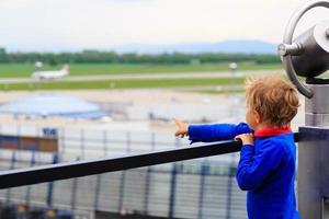 kleine jongen die vliegtuigen op de luchthaven bekijkt