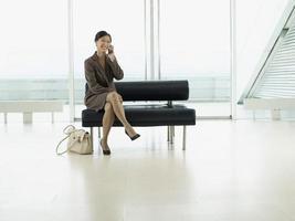 zakenvrouw met behulp van mobiele telefoon in de lobby van de luchthaven foto