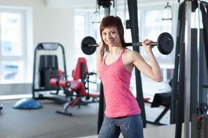 vrouw met barbell in de sportschool foto