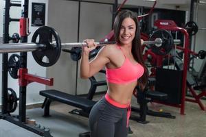 fitness vrouw tillen gewicht in de sportschool foto
