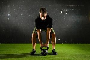 atleet tillen van zwaar gewicht met waterkoker-bel foto