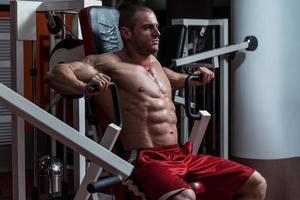 jonge bodybuilder die zwaargewicht oefening voor borst doet