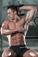 bodybuilder die triceps met domoren uitoefenen