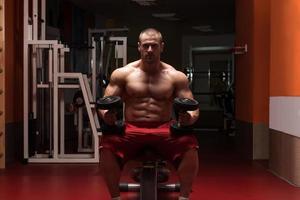 bodybuilder die biceps met domoren uitoefenen