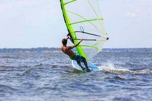 achteraanzicht van jonge windsurfer foto