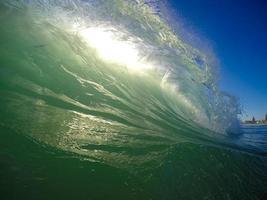 groene glazige golf die op het strand breekt foto