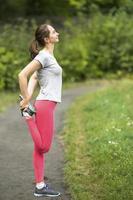 jonge sportieve vrouw oefening warming-up doen voordat joggen in het park foto