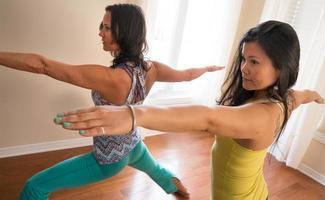 twee yoga vrouwen in krijger 2 poseren foto