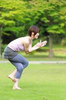 """Japanse vrouw doet yoga """"eagle pose"""" foto"""