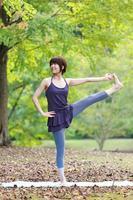 Japanse vrouw doet yoga uitgebreide hand-tot-grote-teen pose foto