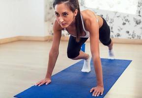 jonge atletische sportieve slanke vrouw die oefeningen op het blauw doet foto
