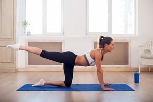 jonge actieve atletische sportieve slanke vrouw doet yoga oefenen de foto