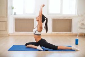 mooie atletische sportieve vrouw in de sportschool doen oefeningen op foto