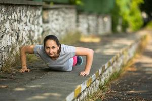 jonge sportieve vrouw doet push-ups in park. foto