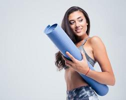 lachende sport vrouw met yoga mat foto