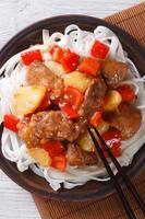 rijstnoedels met varkensvlees in sausclose-up. verticaal bovenaanzicht