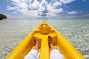 jonge blanke vrouw kajakken in zee op de Maldiven foto