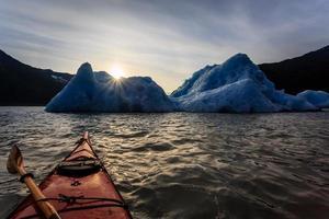 kajak en ijsberg bij zonsondergang