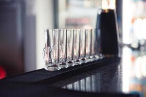 rij van glas shots bij bar foto