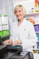 glimlachende apotheker die computer met behulp van foto