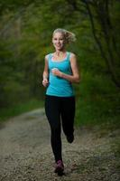 mooie jonge vrouw loopt in het bos - actieve loper uitgevoerd foto