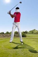een golfer swingende een club op de baan foto