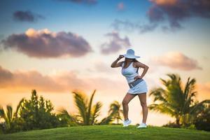 meisje die zich voordeed op de golfbaan in tropische resort foto