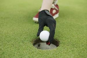 hand die een golfbal van gat neemt foto