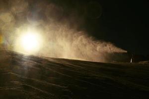 skiër dichtbij sneeuwkanon dat poedersneeuw maakt. Alpen skigebied. foto
